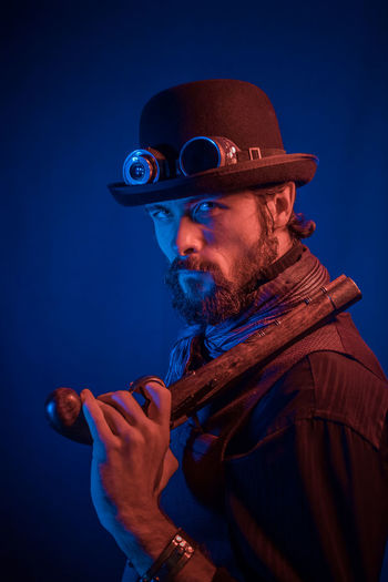Portrait of man wearing hat and aviator glasses with gun against black background