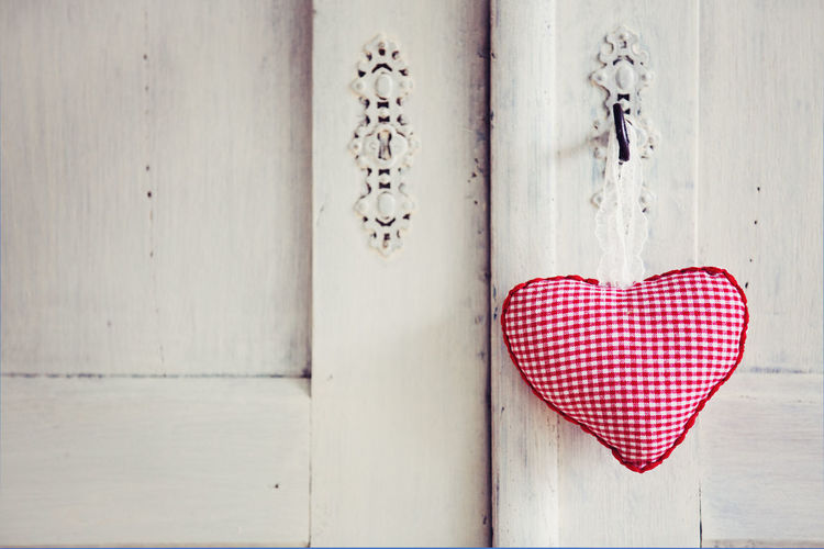 Close-Up Of Handmade Red Heart Shape Cushion Hanging On White Door