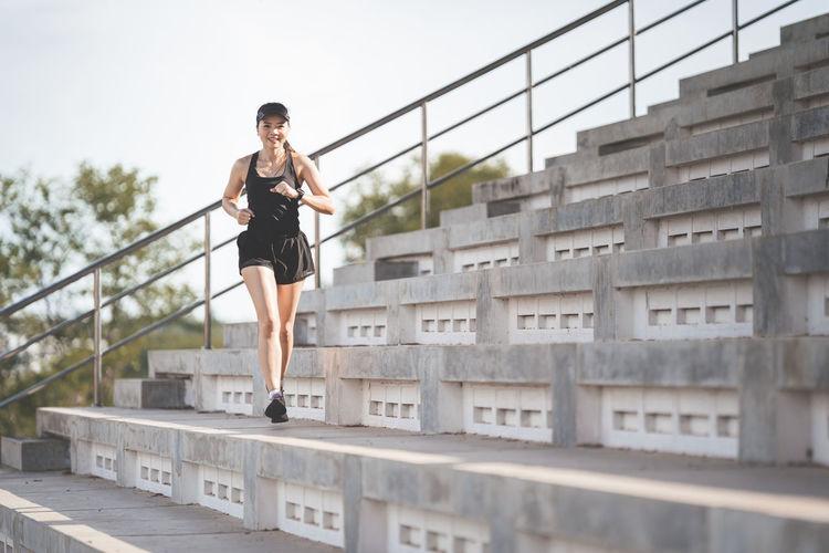 Full length of woman on railing against bridge in city