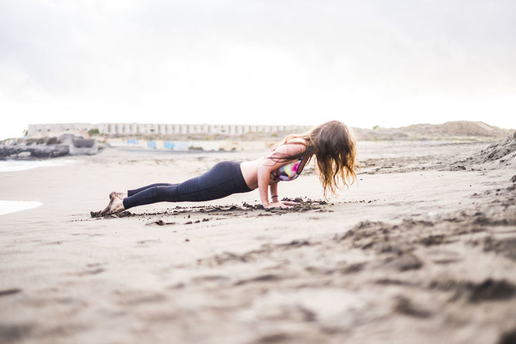 Side view of woman exercising at beach against sky