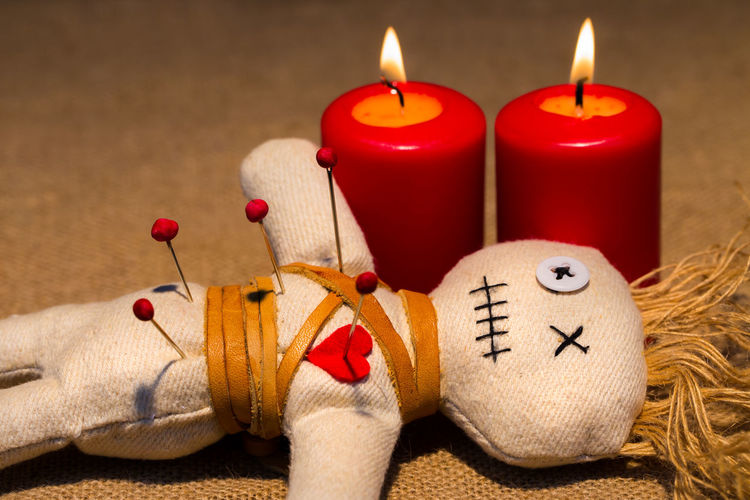 Close-up of spooky doll with illuminated candles