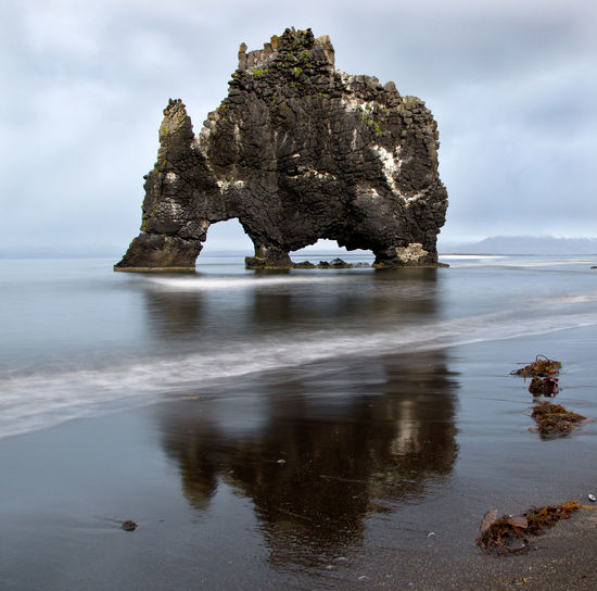 Water Rock Rock - Object Rock Formation Beauty In Nature Solid Tranquility Tranquil Scene Nature No People Scenics - Nature Sea Reflection Day Cloud - Sky Beach Outdoors Natural Arch Eroded Rhinoceroses Tourist Attraction