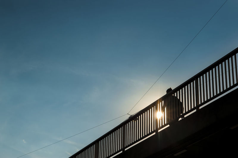 Low Angle View Of Silhouette Person Walking On Bridge Against Blue Sky