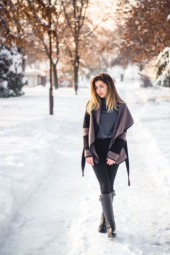 Full length portrait of young woman standing in snow