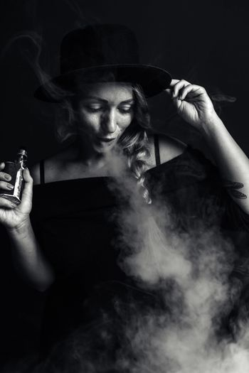 Young Woman Smoking Electronic Cigarette Against Black Background