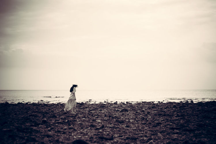 Depression concept black and white young woman standing alone on beach