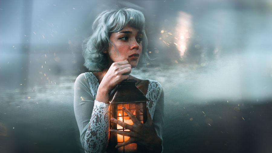 Close-up portrait of young woman holding illuminated while standing in fog