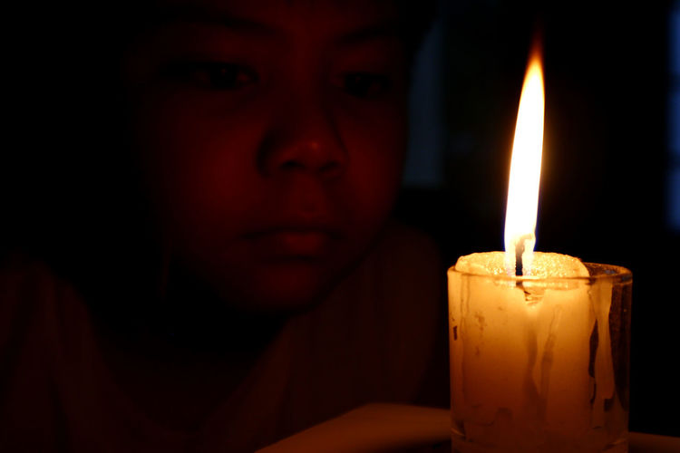 Close-up of boy looking at lit candle in darkroom