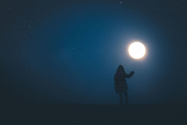 Optical illusion of woman holding moon at night