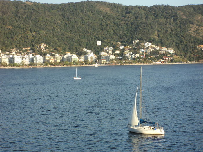 High Angle View Of Sailboat Sailing On Sea Against Mountains