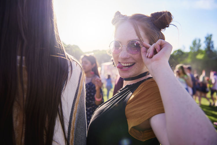 Portrait of young hippy woman in sunglasses at festival Music Festival Traditional Festival Women Boho Summer Outdoors Make A Face Fun Humor Portrait Party Music Sunglasses Fashion Fashionable Traveling Carnival Coachella Valley Young Adult Young Women Sunlight Turning Adult Happiness Joy Toothy Smile Smiling Festival Entertainment Beautiful Woman Copy Space Enjoyment Holiday Live Event Popular Music Concert Look At Camera Youth Culture Vacations Positive Emotion Sunny Waist Up Young Men Weekend Activities