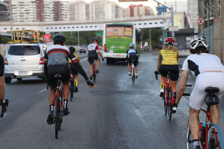 Rear view of people bicycling on road in city