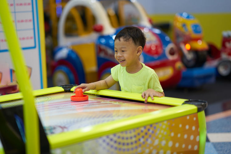 Smiling boy playing air hockey