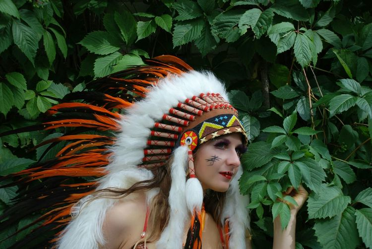 Young woman wearing headdress against plants
