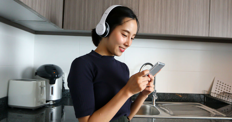 Woman using mobile phone while listening music at home