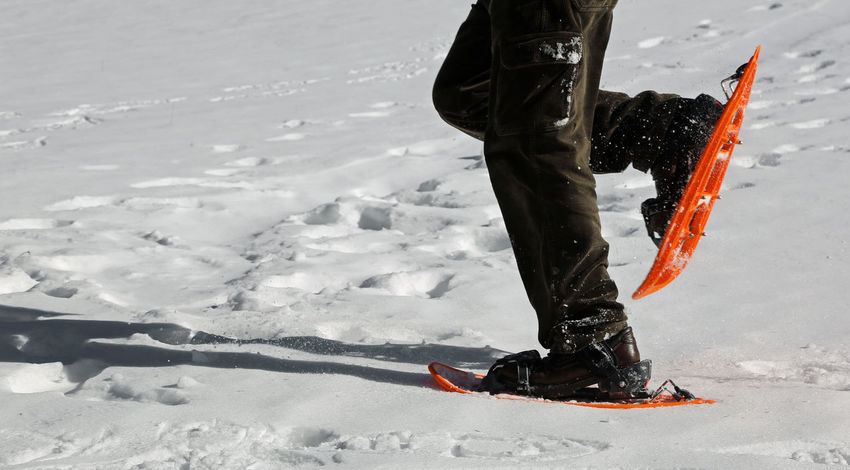 man snowshoeing with orange snowshoes in winter Excursion Life Man Snowshoe Walking Around Winter Adventure Asiago Ciaspolata Ciaspole Close-up Enego Energy Excursions Extreme Sport Extreme Sports Guy Mountain Outdoors Real People Snow Snowshoeing Snowshoes Sportwear Walking