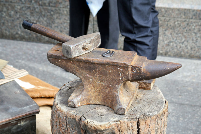 High Angle View Of Anvil With Hammer On Tree Stump