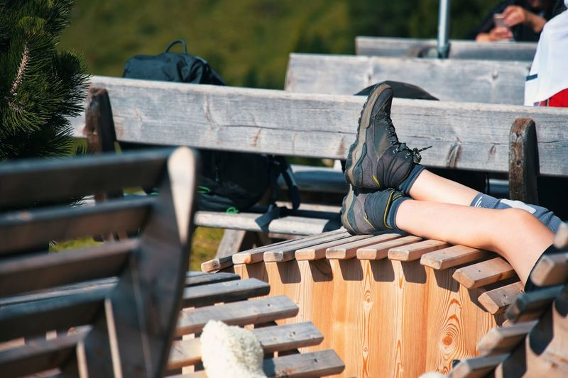 Hiker having rest on wooden chair of mountain hut