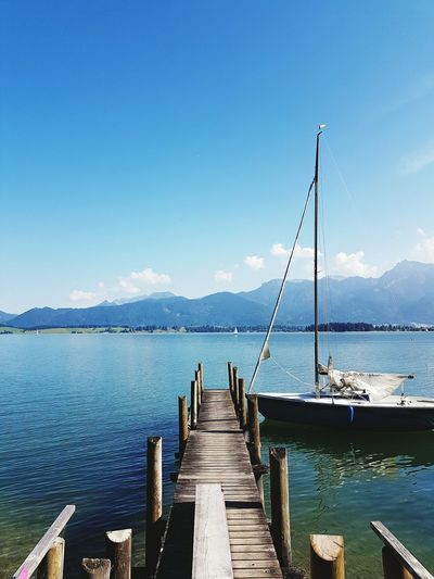 Water Pier Tranquil Scene Mountain Tranquility The Way Forward Calm Jetty Empty Blue Long Wood Paneling Sea Scenics Clear Sky Mountain Range Lake Narrow Ocean Cloud First Eyeem Photo Green Woods No People Forggensee