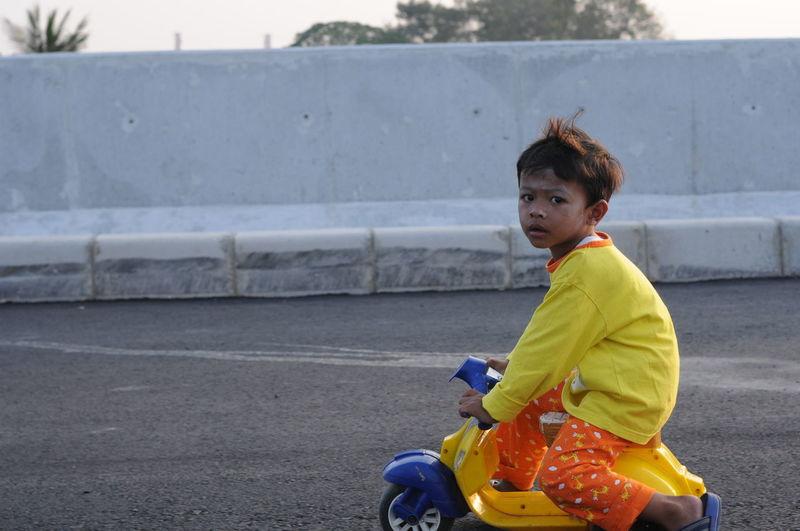 Cute boy sitting on toy car