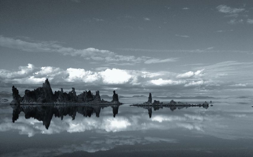 Mid distance of tufa outcrops reflected in calm lake against cloudy sky