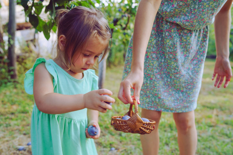 Woman holding easter eggs in basket by daughter standing on grass