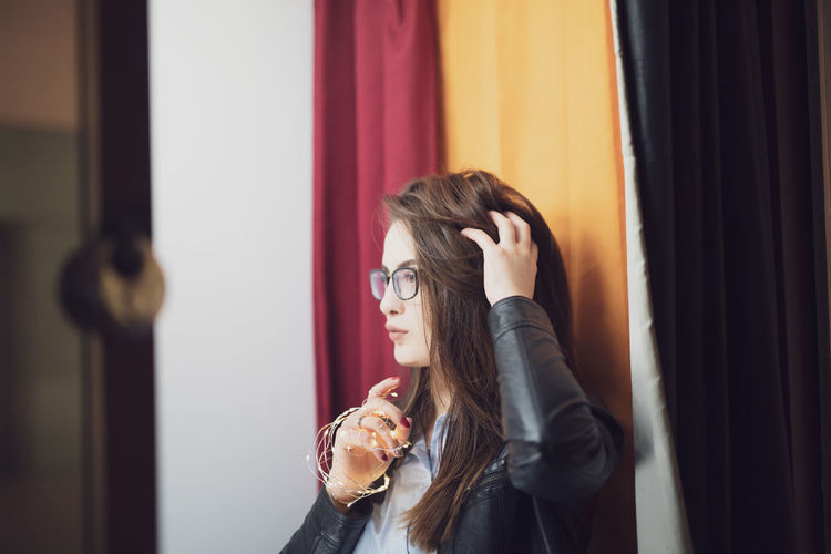 Young woman with hand in hair looking away while standing against curtains at home