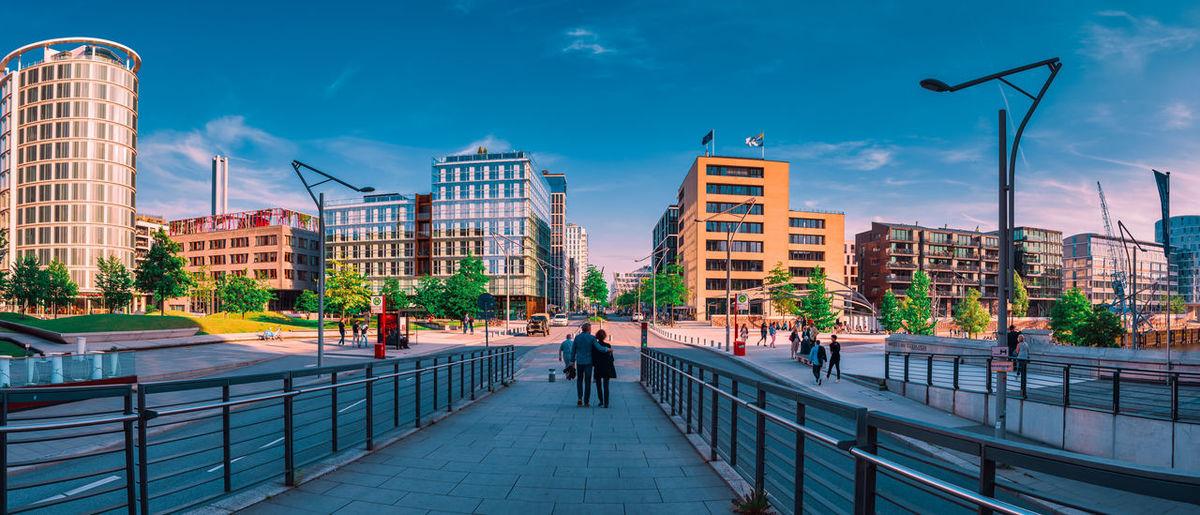 People walking on footpath by buildings in city