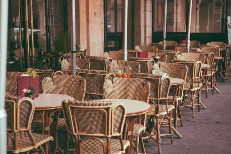 Empty chairs and tables in cafe against building in paris