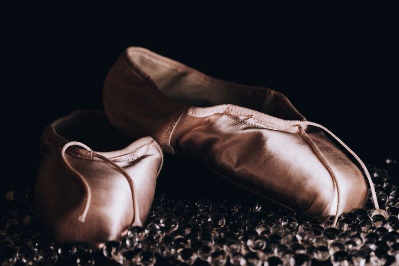 Close-up of ballet shoes against black background