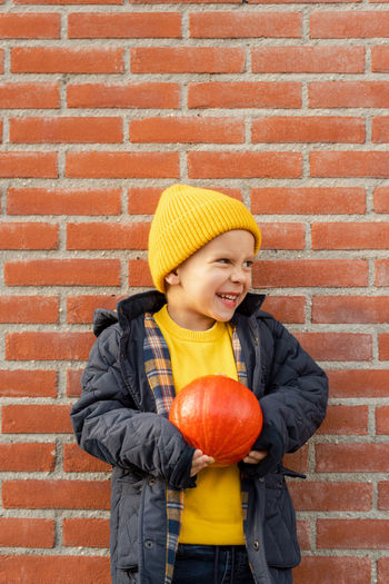 Smiling boy standing against wall