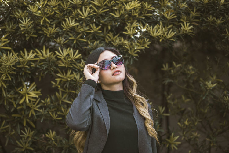 Young woman wearing sunglasses standing by plants