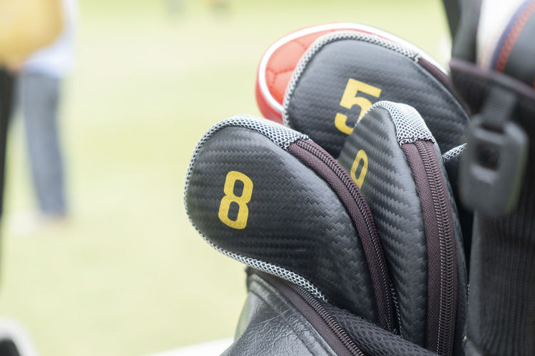 Close-up view of golf club heads in bag Midsection Shoe Human Leg Body Part Human Body Part Sports Equipment Selective Focus Competition Real People One Person Men Rear View Outdoors Clothing Day Sport Focus On Foreground Close-up