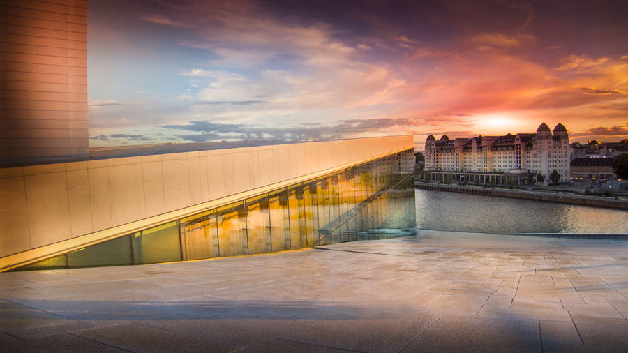 Oslo opera house against cloudy sky during sunset