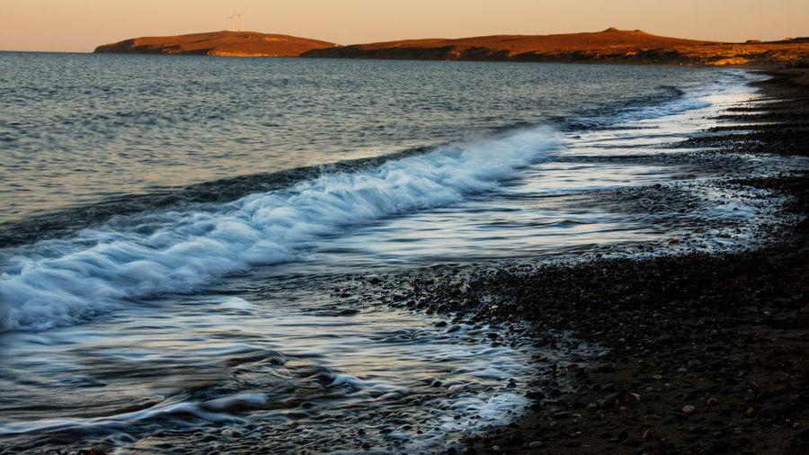 Waves rushing towards shore at sunset