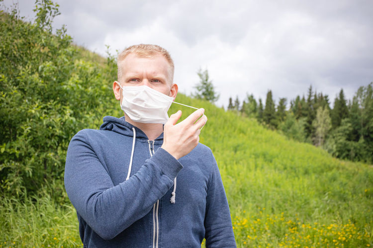Concept of quarantine ending, walks alone. european young male blond removes disposable medical mask