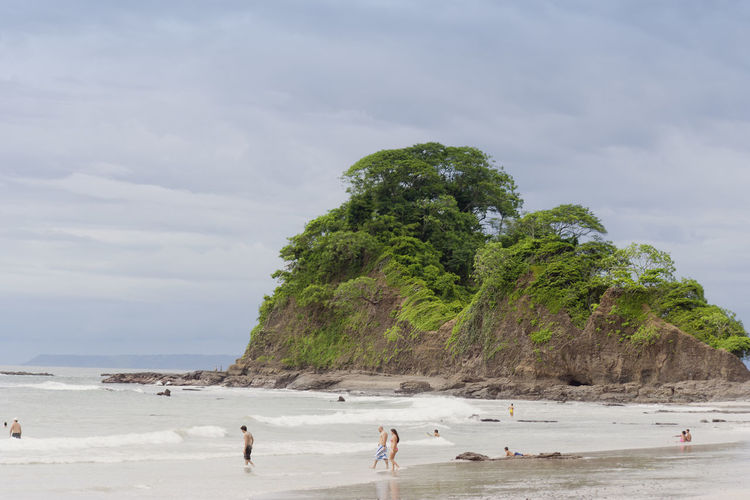 PUNTA LEONA, COSTA RICA - SEPTEMBER 6: People standing in sea at the beach in Punta Leona, Costa Rica. Punta Leona is a leading surfer hotspot with pristine beaches. Been There. Costa Rica Punta Leona Vacations Beach Beauty In Nature Cliff Nature People Sand Scenics Sea Shore Water