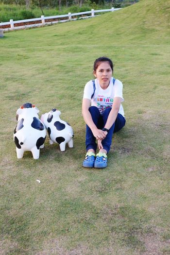 High Angle Portrait Of Woman Sitting On Field By Toy Animal