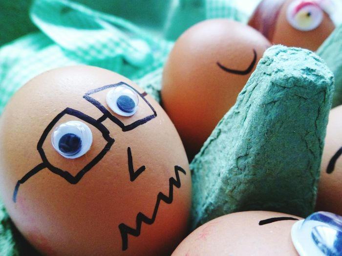 Close-Up Of Artwork On Brown Eggs In Crate