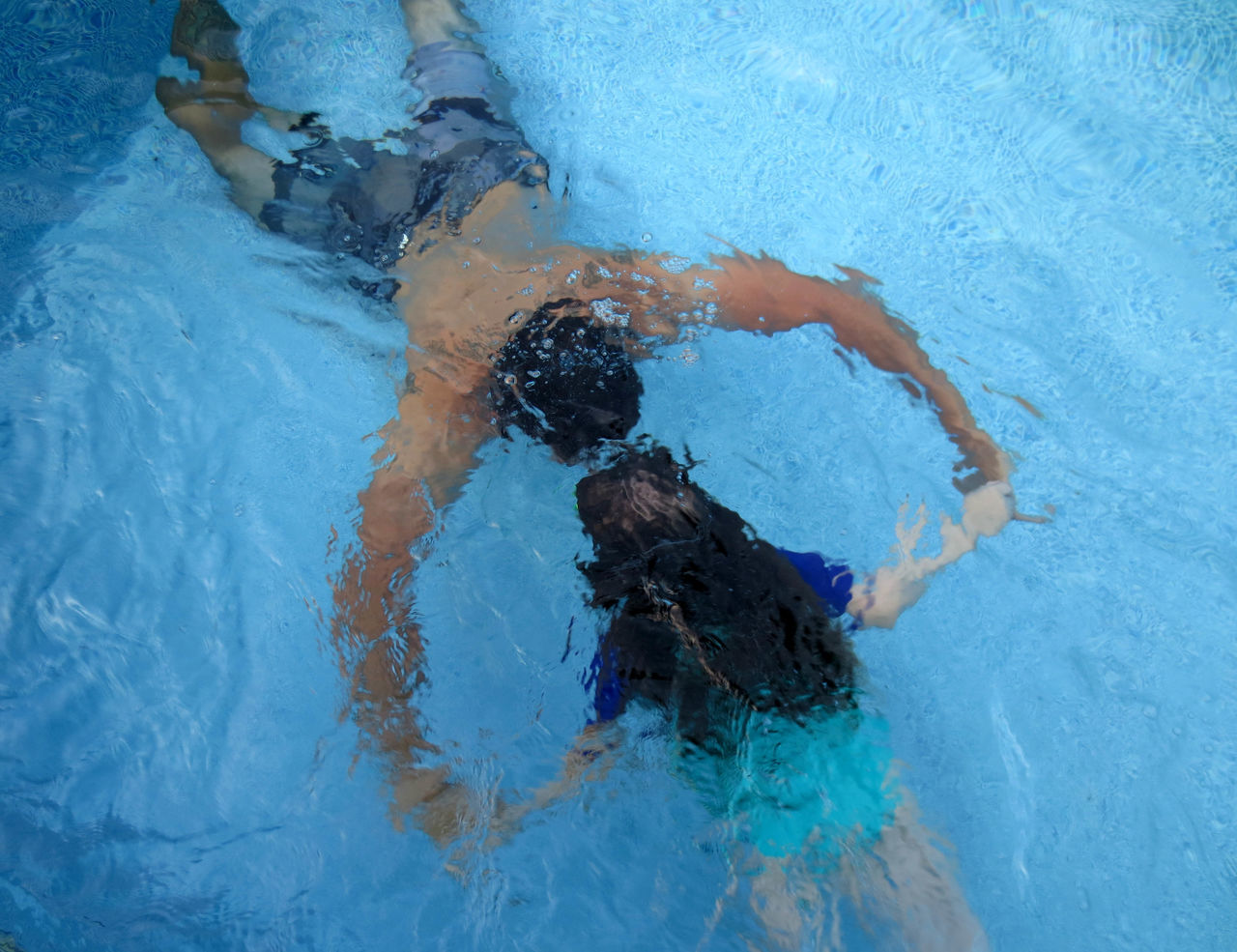 High angle view of father and daughter swimming in pool