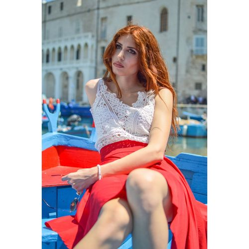 Beautiful Woman Looking Away While Sitting In Boat Against Building In City