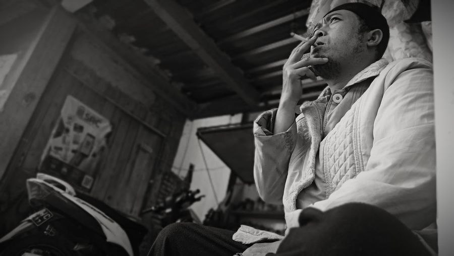 Low angle view of man smoking cigarette while sitting indoors
