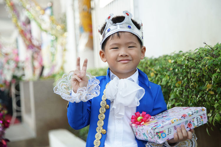Portrait of smiling boy wearing crown holding gift box while standing in party