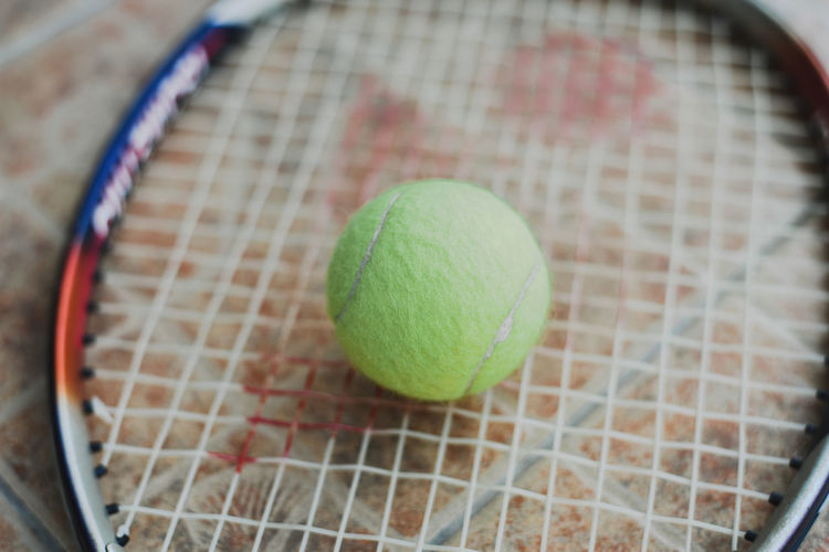 High angle view of tennis ball on tennis racket