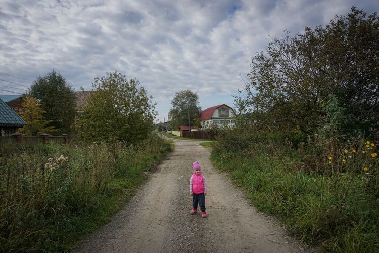Rear view of woman walking on footpath by road against sky