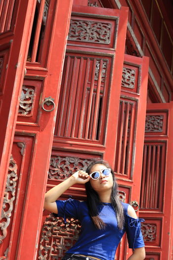 Woman wearing sunglasses while standing by traditional building