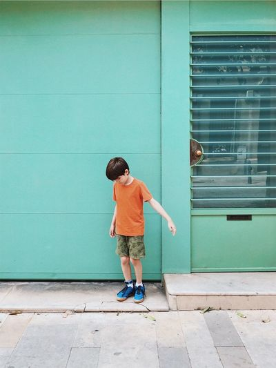 Full length of boy standing on footpath against wall