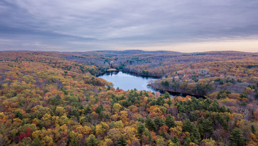 Scenic view of river amidst autumn trees against cloudy sky during sunset