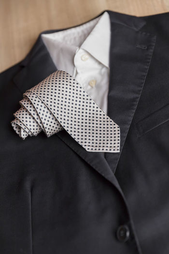 Jacket and tie detail. concept of Italian tailoring. Quality, style, made in Italy. Italy Accessory Background Black Blue Business Businessman Classic Closeup Clothes Clothing Defocused Detail Elégance Elegant Fashion Formal Groom Holiday Italian Jacket Made In Italy Male Man Management Manager Marriage  Material Necktie New No Office People person Professional Shirt Stile Style Suit Table Tailoring Tie Top View Wear White Wood