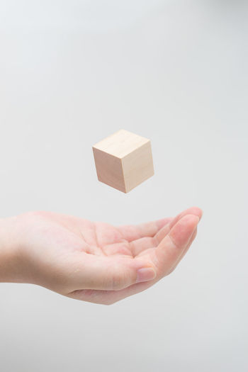 Business concept - Abstract geometric real floating wooden cube on grey background and it's not 3D render. the symbol of leadership, teamwork and growth. Isolated On White Background 3d Rendering Cube Difference  Float Leader Teamwork Abstract Close Up Cubic Different Direction Follow Girl Hand Guide Infographic Leadership Minimalism Simple Surreal Surrealism Team Work Women Wooden Zero Gravity